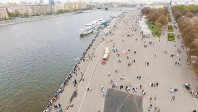 Aerial shot of city river embankment, people walking and relaxing stock video footage