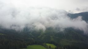 Aerial shot in clouds, camera is over green mountains and fields stock video footage