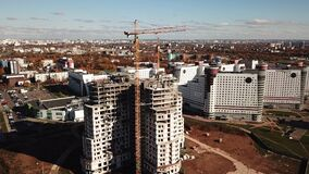 Aerial shot: construction of apartment building in big city center. Two tower crane working on a walls. Autumn time. 4K stock footage