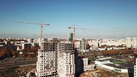 Aerial shot: construction of apartment building in big city center. Two tower crane working on a walls. 4K stock footage
