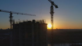 Aerial shot of construction site with cranes and workers at sunset