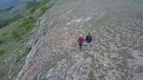 Aerial shot of couple hiking in mountains. Flying over couple hiking near cliff edge stock video footage
