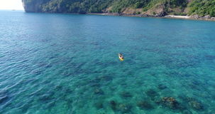 Aerial shot of couple kayaking in turquoise sea during summer day. Travel tropical island holiday concept stock video