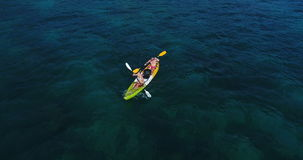 Aerial shot of couple kayaking in turquoise sea during summer day stock video footage