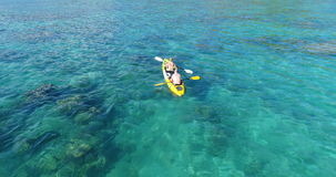 Aerial shot of couple kayaking in turquoise sea during summer day. Travel tropical island holiday concept stock footage