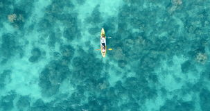 Aerial shot of couple kayaking in turquoise sea during summer day stock footage