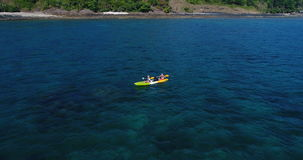 Aerial shot of couple kayaking in turquoise sea during summer day. Travel tropical island holiday concept stock video footage