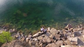 Aerial shot of couple on the lake and hills stock footage