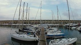 Aerial shot of the docks, with lots of sailing yachts and boats, Malaga, Spain. Nice pier in the docks full of parked yachts and sailing boats, aerial shot stock footage