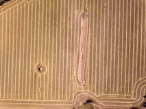 Aerial shot of dry brown farm land and harvest patterns royalty free stock photography