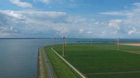 Aerial shot of a Dutch. And a Power Generating Windmills in the polder of Flevoland Almere Pampus on a cloudy windy day stock video footage