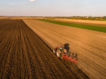 Aerial shot of a farmer plowing stubble field Royalty Free Stock Photos