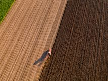 Aerial shot of a farmer plowing stubble field Royalty Free Stock Images