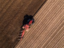Aerial shot of a farmer plowing stubble field royalty free stock image