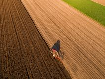 Aerial shot of a farmer plowing stubble field stock photos