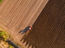 Aerial shot of a farmer plowing stubble field stock photo
