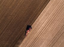Aerial shot of a farmer plowing stubble field Royalty Free Stock Photo