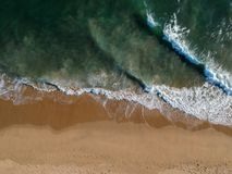 Breaking waves and sandy waters Royalty Free Stock Photography