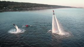 Aerial shot of Flyboarding. Two athletes fly on flyboards above the water. Men perform various tricks and turns. Extreme stock video footage
