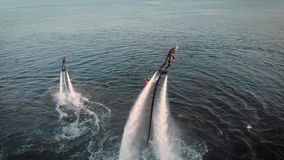 Aerial shot of Flyboarding. Two athletes fly on flyboards above the water. Men perform various tricks and turns. Extreme stock footage