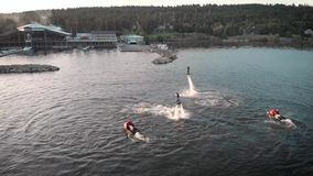 Aerial shot of Flyboarding. Two athletes fly on flyboards above the water. Men perform various tricks and turns. Extreme stock video