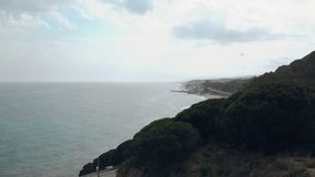 Aerial shot of flying above the hill and the road with Mediteranean sea in the background stock footage