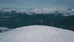 Aerial shot flying over winner male snowboarder admiring mountain landscape from peak of rock