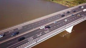 Aerial shot focuses on the traffic on the bridge. Cars driving. Cars crossing the bridge. 4K. Sun shining. Cars stock video