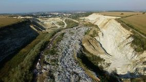 Aerial shot of garbage dump between agricultural fields. Drone fly above trush stock video