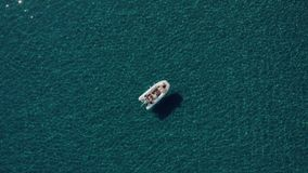 Aerial shot of happy couple relaxing and sunbathing on a boat parked in the middle of the most clean Mediterranean water stock video