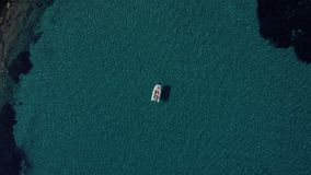 Aerial shot of happy couple relaxing and sunbathing on a boat parked in the middle of the most clean Mediterranean water stock video footage