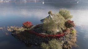 Aerial shot of Hexagonal japanese temple built in 1200`s in Fuji lakes area Japan. Autumn, fall red maple leaves and glisten. Ing water stock video footage