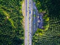 Aerial shot highway, road with forest, farm. Moving vehicles Royalty Free Stock Photography