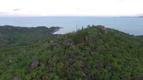 Island forest and ocean aerial shot. A aerial shot of a house on top. Camera goes backwards to show a much larger view of the island forest stock video footage