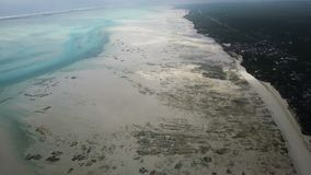 Aerial shot Jambiani Beach at Low tide in the Zanzibar. Large outflows on the island stock footage