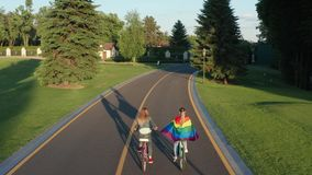 Aerial shot of lgbt couple biking on bicycle lane. Rear drone view of young lesbian couple enjoying joint weekend leisure riding bicycles along bike path in stock video footage