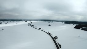 Aerial shot of a lonely road winding trough the snow on a cloudy winter day. Drone moves along road, street stock video footage