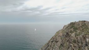 Aerial shot of a lonely yacht sailing on the sea, with huge rock in the foreground stock footage
