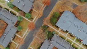 Aerial shot looking down on urban housing development - housing estate of yellow trees and roof tops. Aerial shot looking down on urban housing development of stock video footage
