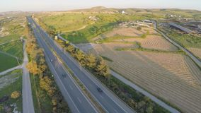 Aerial shot of many trees, harvested farming fields, green hills along highway. Stock footage stock footage