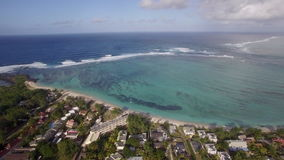 Aerial shot of Mauritius coast and Indian Ocean. Aerial view of Mauritius with farmlands and houses along the coast. Resorts at beautiful lagoon with clear blue stock video footage