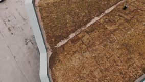 Aerial shot of modern architect building roof covered in soil in suburbs. Aerial shot of modern architect building pyramid roof covered in soil, dry grass and stock footage