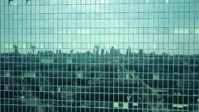 Aerial shot of modern office building windows reflecting cityscape on a sunny day. 4K video stock video