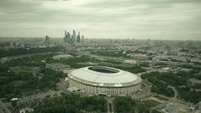 Aerial shot of Moscow cityscape involving famous Luzhniki football stadium and distant business center skyscrapes Stock Photo