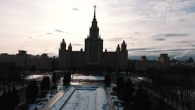 Aerial shot of Moscow State University building silhouette, snow covered park stock video