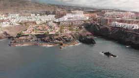Aerial Shot. Mountain resort town with many hotels, palm trees and other vegetation. Blue ocean and the waves beating on stock video