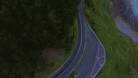Aerial shot of mountain road. Top view drone footage of empty mountain road winding near the shore of cliffs and rocks dropping into ocean, lonely cars ride stock footage