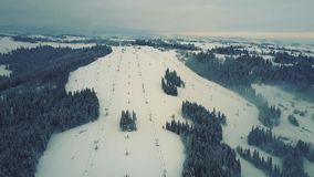 Aerial shot of mountain ski slopes and lifts in the snow. Aerial view of alpine skiing slopes and ski lifts in winter stock video footage