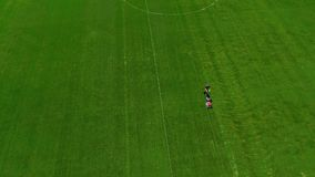 Aerial shot of mowing grass in a football stadium. 4K stock video footage