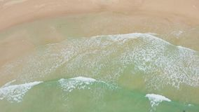Aerial shot of ocean waves crashing against an beautiful beach. Aerial shot of ocean waves crashing against an beautiful beach stock footage